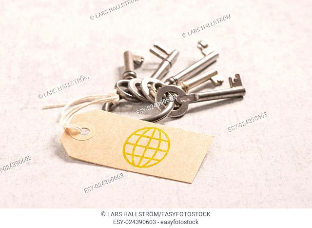 Vintage key set and symbol of world business network on paper tag. Concept of travel, connection and logistics
