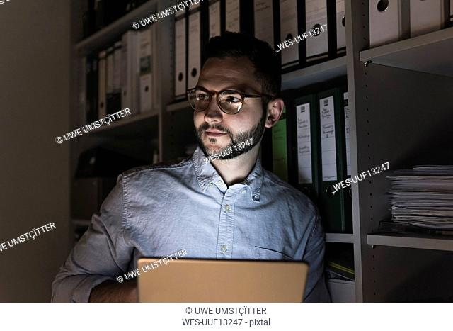 Portrait of businessman with tablet working late in office
