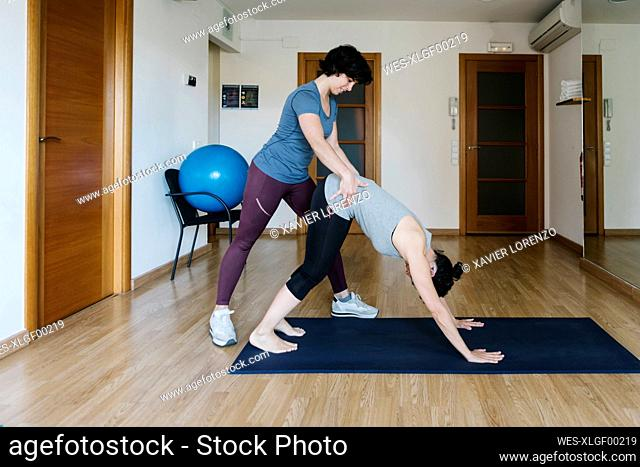 Physiotherapist assisting patient in bending on mat at health club