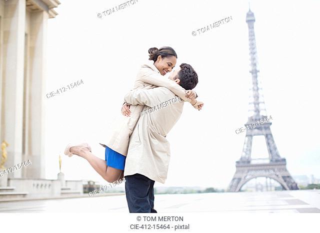 Couple hugging near Eiffel Tower, Paris, France