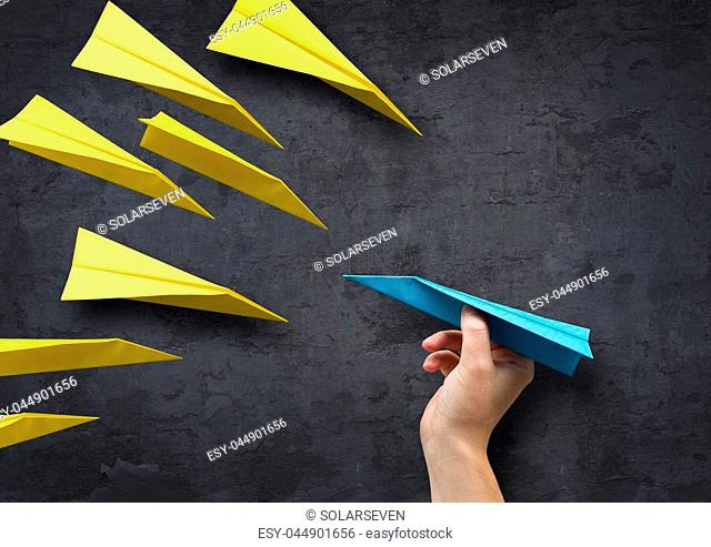 Concept - Being different. A man about to throw a paper plane in a different direction to everyone else