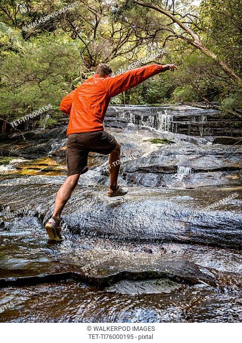 Australia, New South Wales, Katoomba, Man running on rocks of Leura Cascade