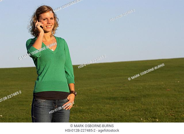 Young blonde woman outdoors talking on cellphone