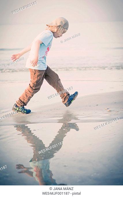 Germany, Mecklenburg-Western Pomerania, Ruegen, Boy walking at the ocean