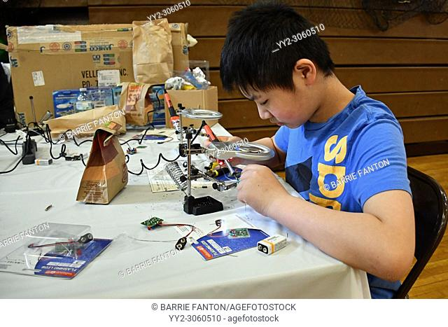 Student Using Magnifier for Soldering at Maker Faire, Wellsville, New York, USA