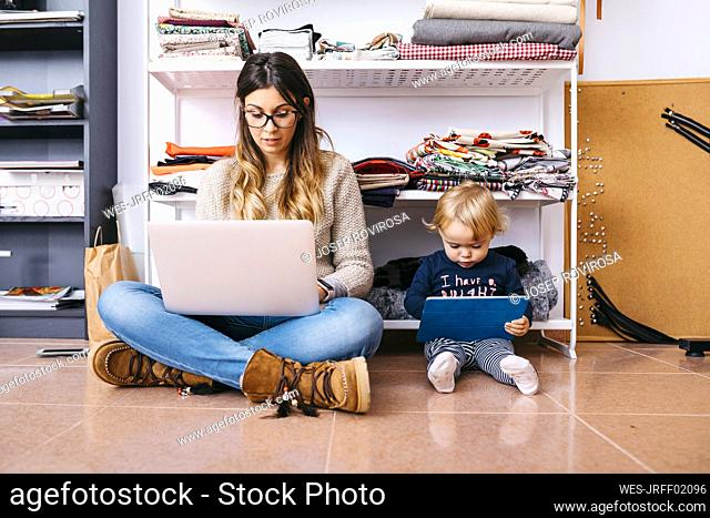 Mother and little daughter sitting on the floor at home using laptop and tablet
