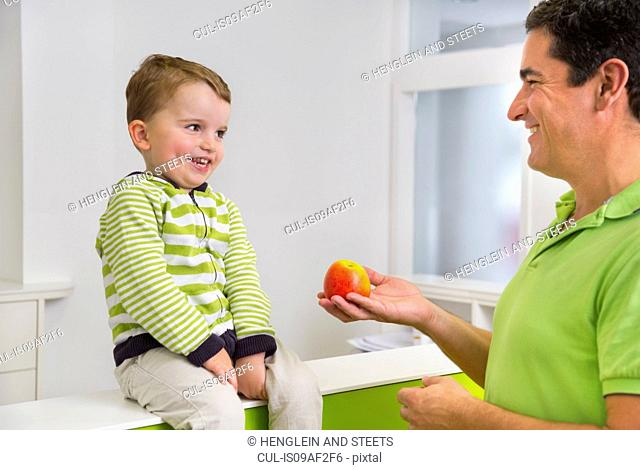 Man giving young boy apple