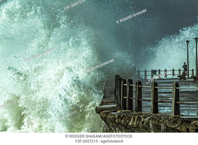 A man runs on a promenade at the seaside during a storm with huge wave breaking over the seawall. Sea Point, Cape Town, South Africa