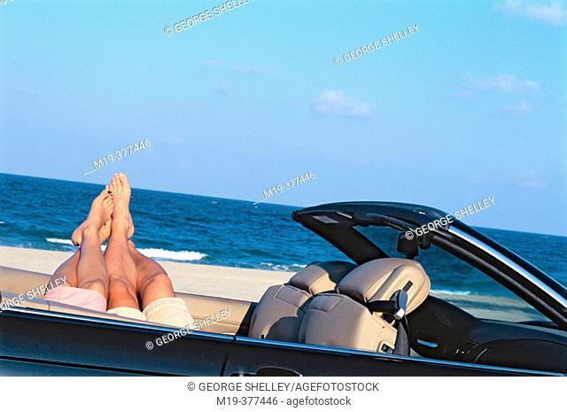 couple in a convertible relaxing at the beach