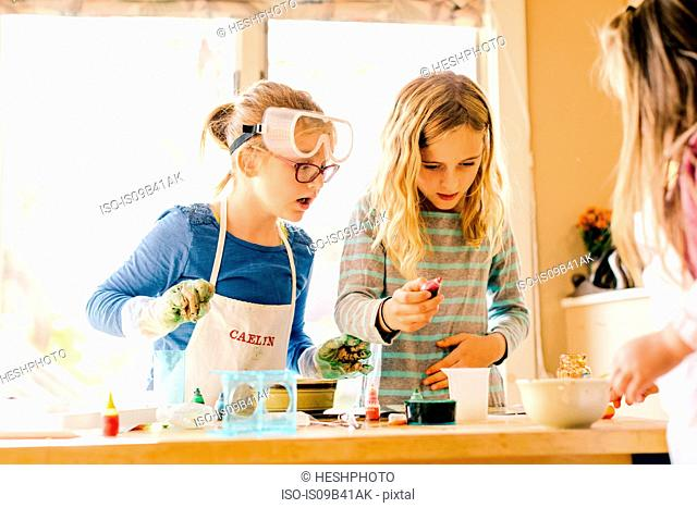 Three surprised girls doing science experiment, staring