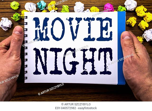 Writing text showing Movie Night. Business concept for Wathing Movies written notepad notebook book on the wooden wood background with man businessman hand and...