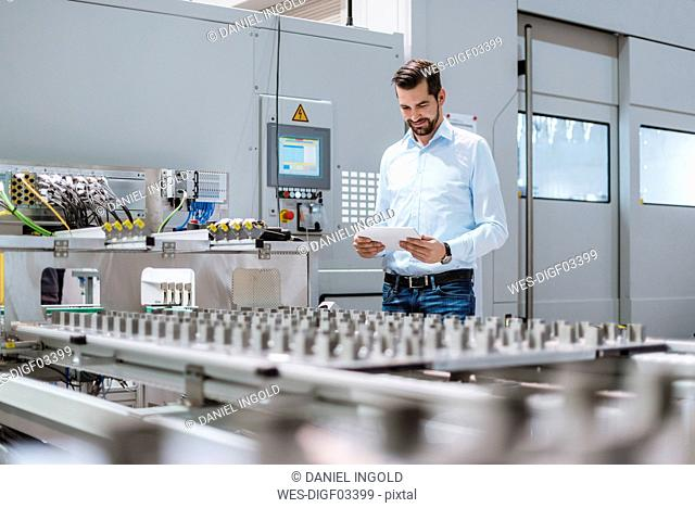 Businessman at machine in factory looking at tablet