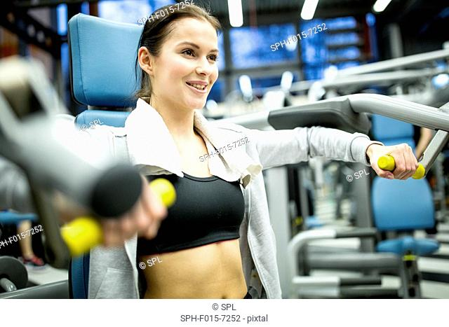 MODEL RELEASED. Young woman smiling and using exercising machine in gym