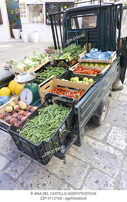 Cityscape in Ostuni Brindisi Puglia Italy on July 13, 2018. Greengrocers in a three-wheeled motorcycle