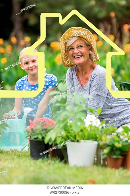 Grandmother and granddaughter watering plants in garden against house outline in background