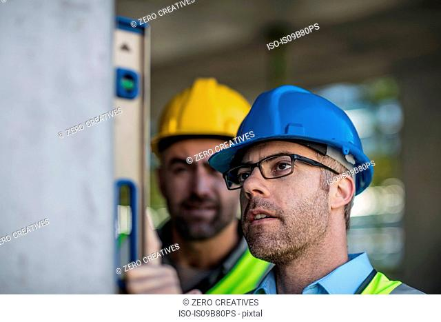 Project manager and construction worker using spirit level