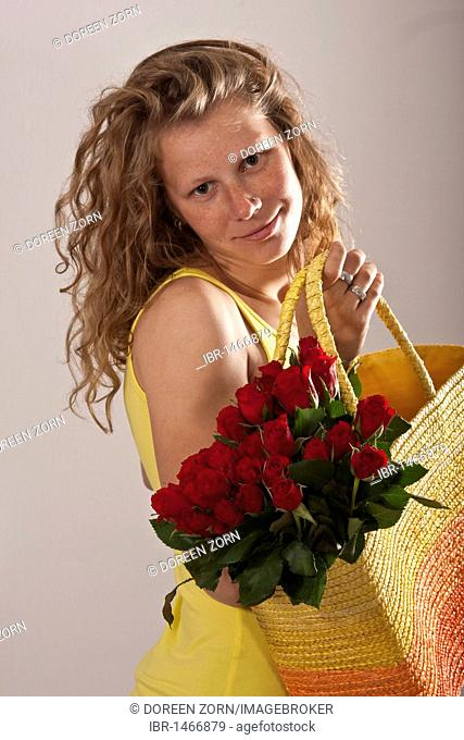 Woman with a bouquet of roses in a bag