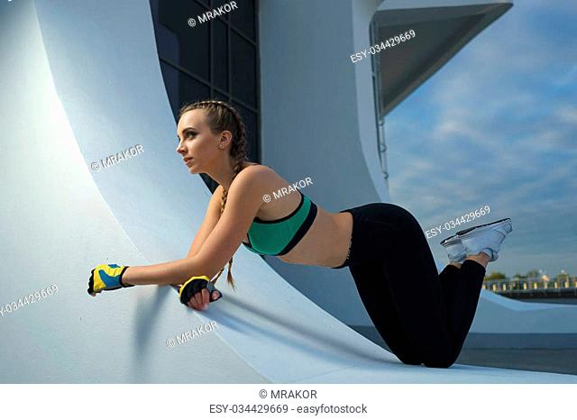 Concept: healthy lifestyle, sport. Attractive happy girl fitness trainer do outdoor workout at modern downtown urban area during sunset