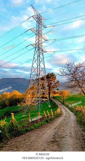 Electric power line and a track in a rural landscape near Ceceda village, Nava municipality, Asturias, Spain