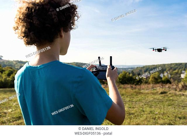 Boy navigating a flying drone outdoors