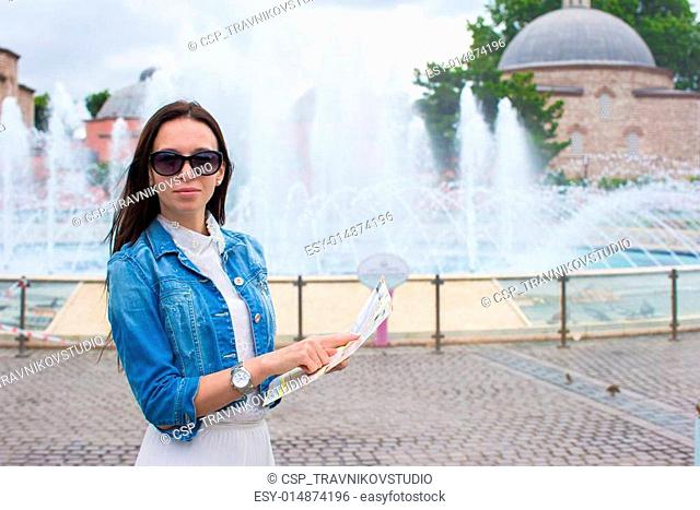 Young beautiful traveling woman with map of city in hands