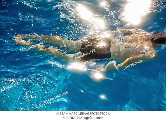 A man underwater swimming as sunlight reflects off the bright blue water