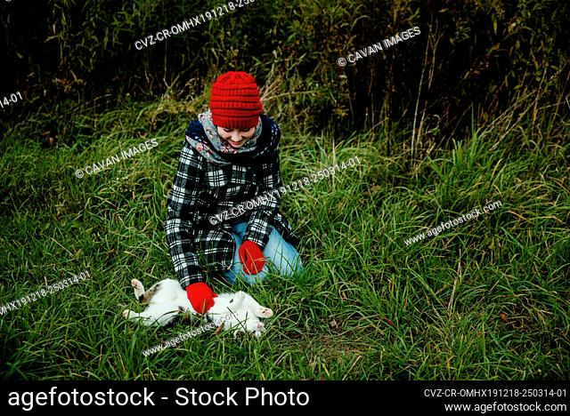Girl Smiling as she Pets Her Cats Stomach Outdoors in the Grass
