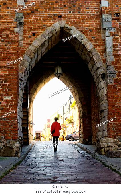 Young woman and gate of Sandomierz - Poland