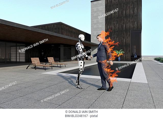 Burning businessman handshaking with cyborg