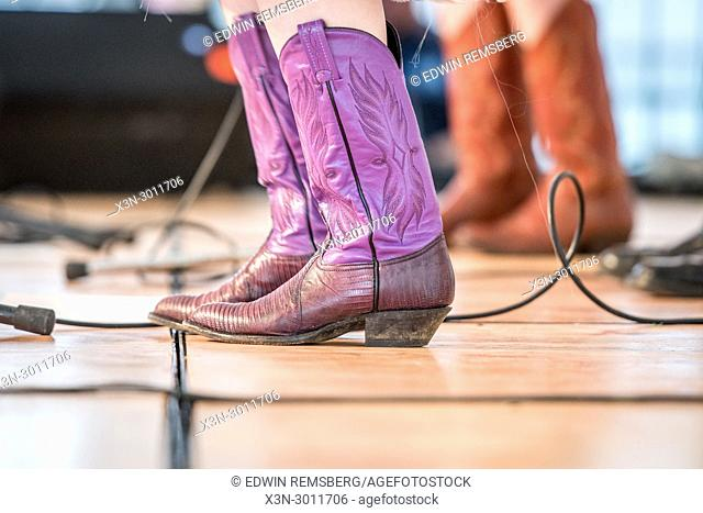 Detailed shot of purple cowboy boots with an audio cable running behind them on stage, Greensboro, North Carolina. USA