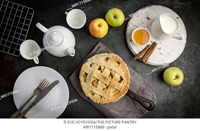 Apple Pie on iron skillet with tea and honey. Top view