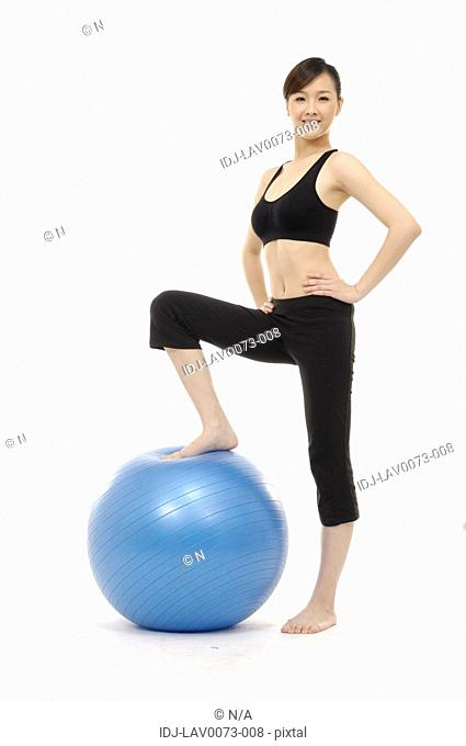 Woman standing with one foot on large blue rubber ball