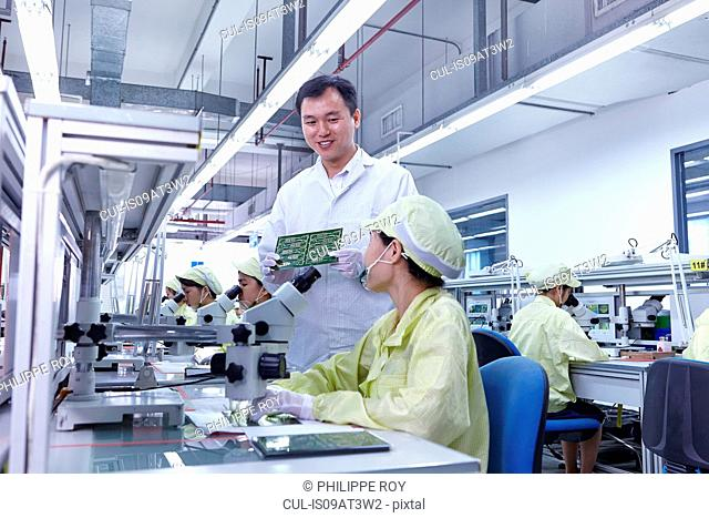 Supervisor overseeing quality check station at factory producing flexible electronic circuit boards. Plant is located in the south of China, in Zhuhai