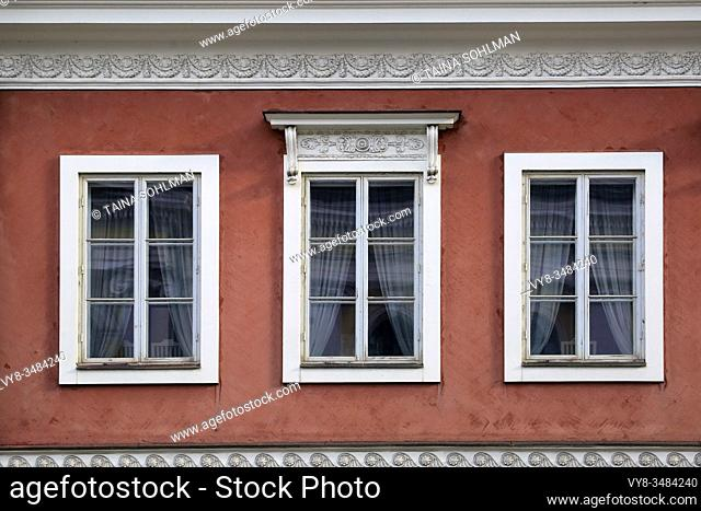 Detail of three windows on the exterior of a red, classic, historic city building in Helsinki, Finland. Light alterations in post production