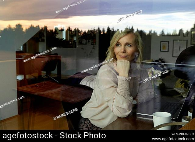 Portrait of blond woman with laptop behind windowpane at home