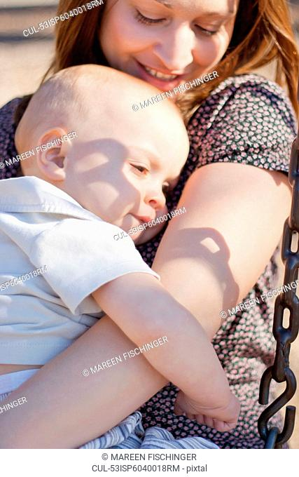 Mother holding baby boy on swing