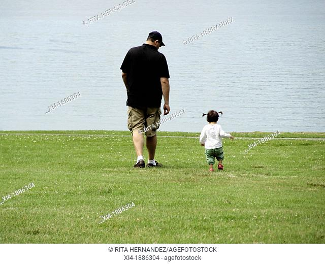 Father walking toward the sea with little daughter beside him