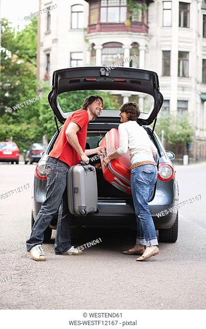 Germany, Leipzig, Couple loading luggage into car