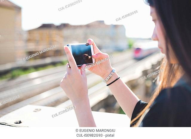 Young woman on city roof terrace looking at smartphone