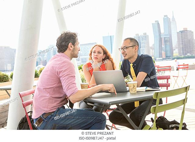 Businessmen and woman using laptop at waterfront cafe, New York, USA