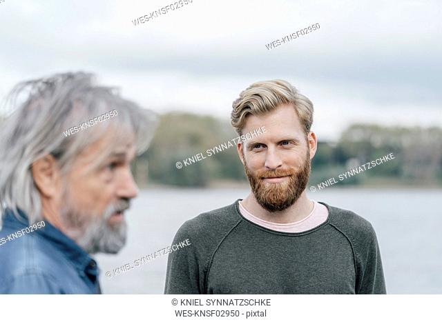 Father and son meeting outdoors, portrait