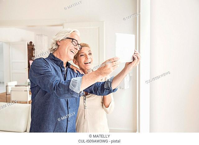 Couple taking self portrait, using digital tablet