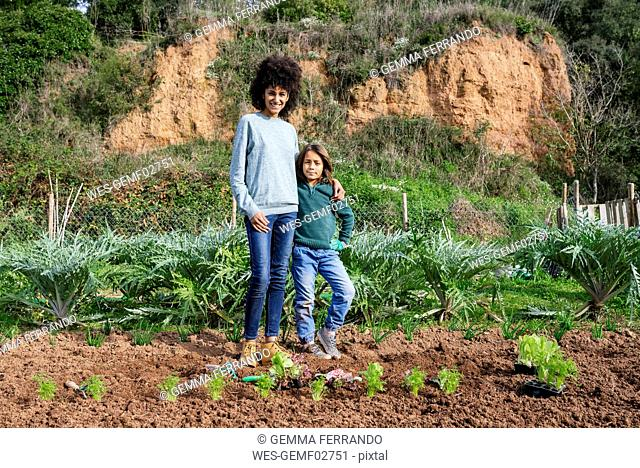 Mother and son standing in vegetable garden with lettuce seedlings