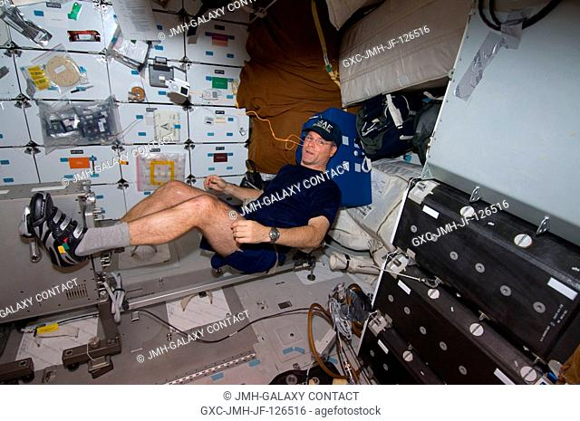 Astronaut Kevin Ford, STS-128 pilot, works out on the bicycle ergometer on the middeck of the Space Shuttle Discovery. The shuttle is currently docked with the...