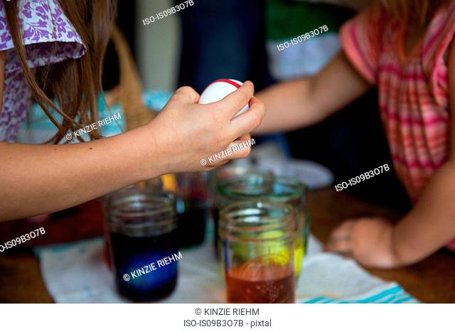 Hands of two young sisters preparing to dye easter eggs in jars at table