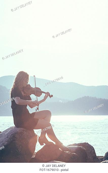 Woman playing violin while sitting on rock at lakeshore against clear sky
