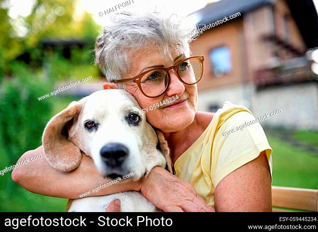 Portrait of senior woman sitting and resting outdoors in garden, holding pet dog