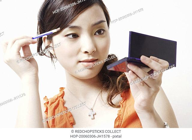 Close-up of a young woman holding a make-up brush and a hand mirror