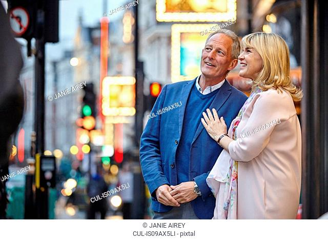 Mature dating couple looking up from city street at dusk, London, UK
