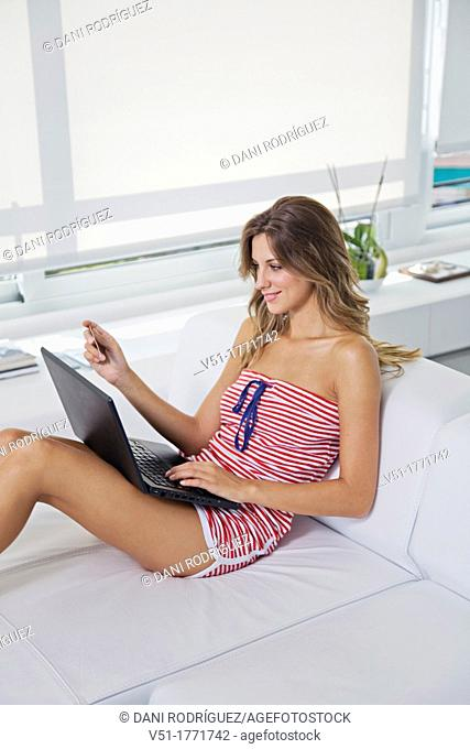 Pretty blonde woman with laptop in the living room